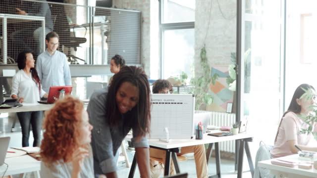 vídeos de stock, filmes e b-roll de diretor sênior da arte que mentoring o estagiário novo no escritório moderno - coworking space