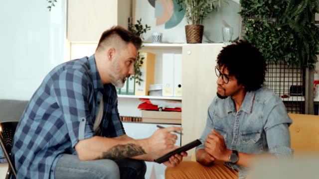 senior art director mentoring new intern - honesty stock videos & royalty-free footage