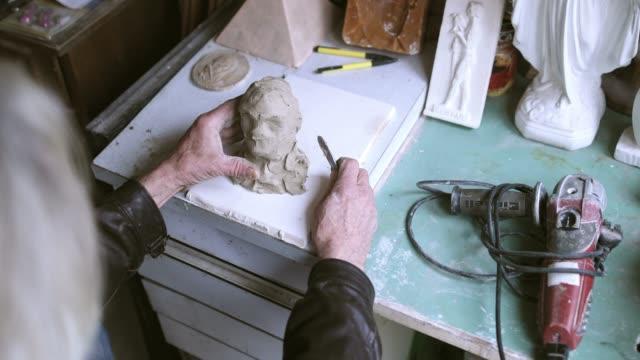 stockvideo's en b-roll-footage met senior kunstenaar te maken beeldhouwkunst binnenshuis - carving craft product