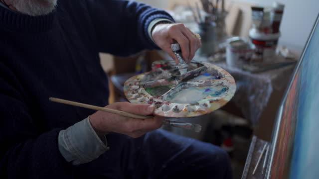 vídeos de stock, filmes e b-roll de artista sênior que mistura cores na paleta do artista - painter artist
