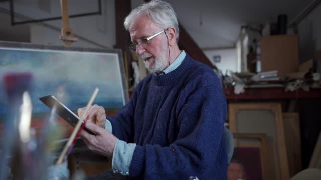 vídeos de stock, filmes e b-roll de artista sênior que usa a tecnologia para melhores resultados - painter artist