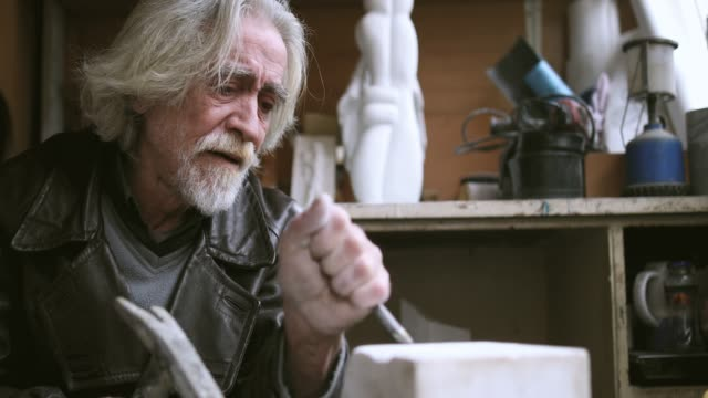 vídeos de stock e filmes b-roll de senior artist working with marble at his workshop - escultura