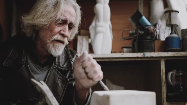senior artist working with marble at his workshop - passione video stock e b–roll