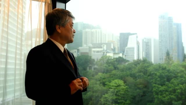 vídeos de stock, filmes e b-roll de empresário asiático sênior, preparando-se em seu hotel - etnia oriental