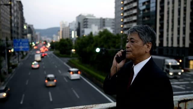 アジアの老人実業家話す、携帯電話街の - senior men点の映像素材/bロール