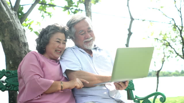 Senior asian couple holding  notebook to face time with their chlidren