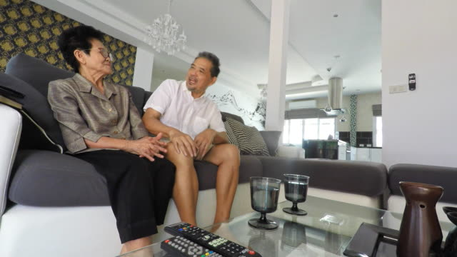 senior asian couple talking at home - eurasian ethnicity stock videos and b-roll footage