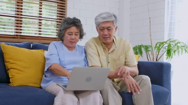 vídeos de stock, filmes e b-roll de sénior asiática casal usando computador portátil e exploração de cartão de crédito para compras on-line em casa, estilos de vida aposentadoria e tecnologia - idoso na internet