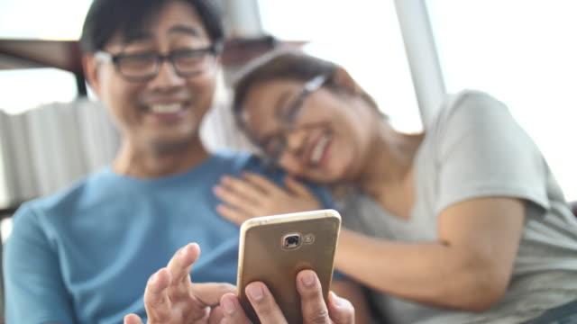 vídeos de stock e filmes b-roll de senior asian couple using mobile phone - perto