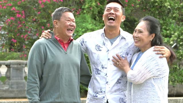 senior asian couple with adult son laughing in park - adult offspring stock videos & royalty-free footage