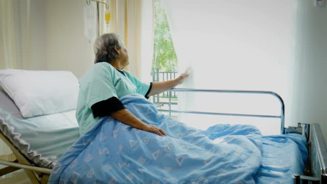 vídeos de stock, filmes e b-roll de sênior asiática feminina paciente sentada e deitada na cama sozinha no quarto do hospital - condição médica