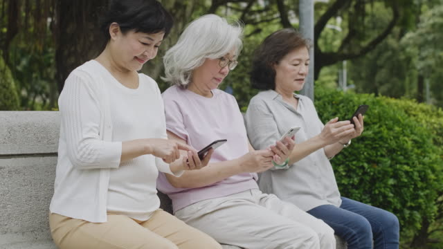 senior asian females browsing smart phones at park - surfing the net stock videos & royalty-free footage
