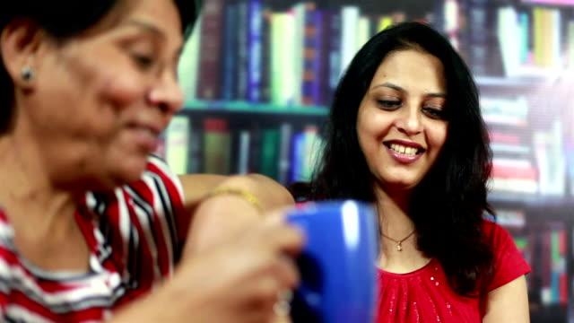 Senior asiatischen, indischen und junge Frau Schwätzchen mit Kaffee