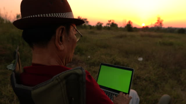 senior asian male a relax at sunset with looking at a green screen chroma key computer screen - over the shoulder stock videos & royalty-free footage