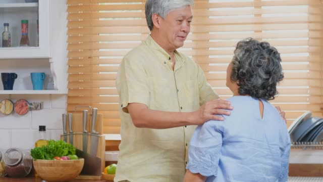 senior asian man comforting the depression senior woman while standing in kitchen at home, retirement people emotional - sad old asian man stock videos & royalty-free footage
