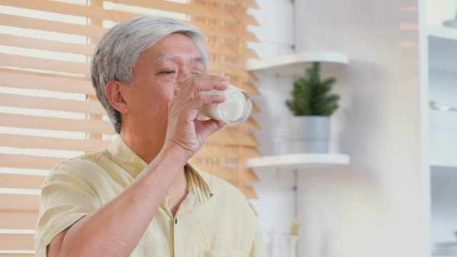 senior asian man drinking milk in kitchen at home, retirement lifestyle, active senior healthy - soy milk almond milk stock videos & royalty-free footage
