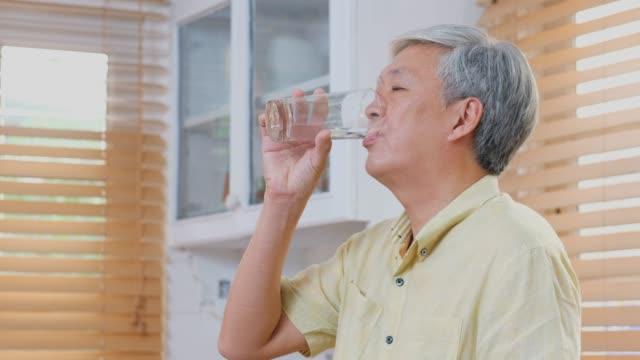 vídeos de stock, filmes e b-roll de água bebendo do homem asiático sênior na cozinha, povos sênior em casa estilos de vida, sénior ativo saudável - água potável