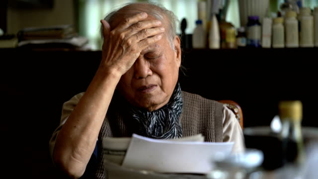 senior asian man feeling headache and tired eyes after reading too much - east asian ethnicity stock videos & royalty-free footage