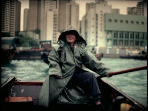 vídeos de stock, filmes e b-roll de senior asian man in hooded raincoat steering boat from back / skyscrapers in background / hong kong - superexposto