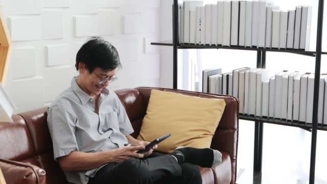 senior asian man playing tablet and asian elderly man is relaxing and happiness with video call  on sofa in living room at home - hot desking stock videos & royalty-free footage