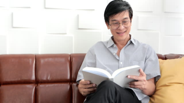 senior asian man reading book on sofa in living room at home ,asian elderly man is relaxing and happiness with read a magazine - open magazine stock videos & royalty-free footage