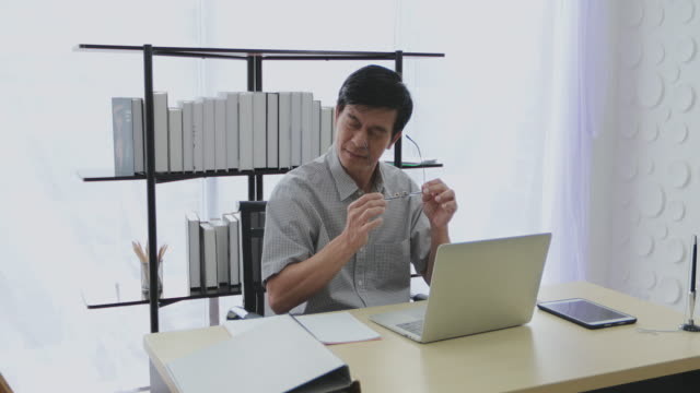 a senior asian man uses a calculator and works hard until stressed. - southeast asia stock videos & royalty-free footage