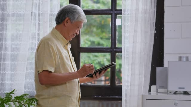 senior asian man using digital tablet  with happiness while standing by window at home, daily retirement technology and lifestyle - online banking video stock e b–roll