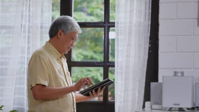 vídeos de stock e filmes b-roll de senior asian man using digital tablet  with happiness while standing by window at home, daily retirement technology and lifestyle - idoso na internet