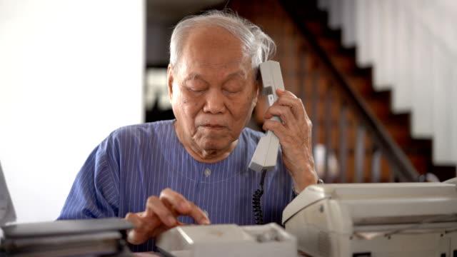 senior asian man using retro telephone at home - fax machine stock videos & royalty-free footage