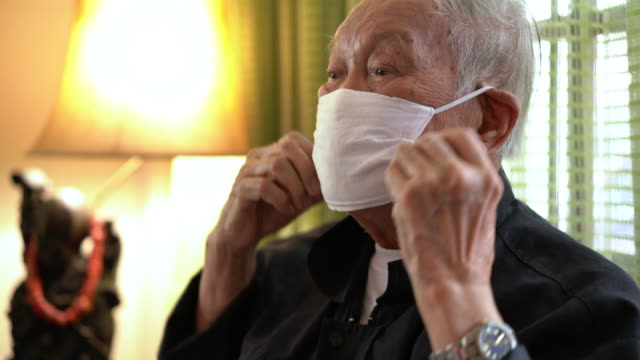 senior asian man wearing air pollution mask at home - asian man coughing stock videos & royalty-free footage