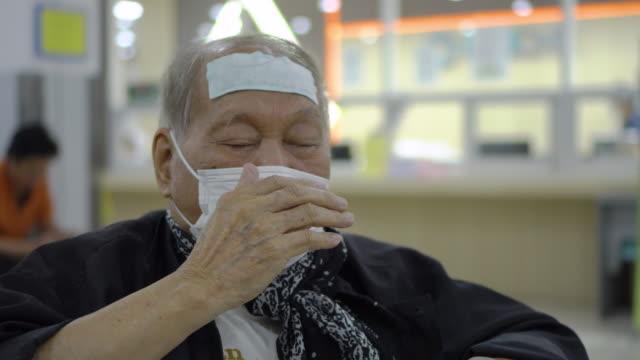 senior asian man wearing mask coughing while waiting at hospital - asian man coughing stock videos & royalty-free footage