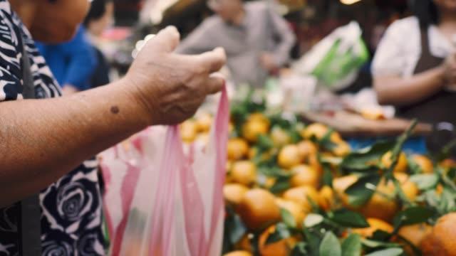 Senior Aziatische vrouw kopen van groenten en fruit stand op de boeren markt plaats