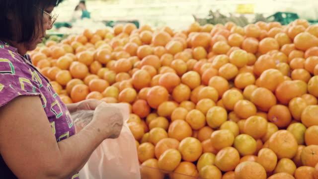 senior asian woman buying fruits and vegetables stand - mercato di prodotti agricoli video stock e b–roll