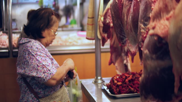 senior asian woman buying meat and pork at the farmers market place - butcher stock videos & royalty-free footage