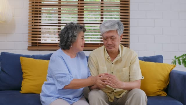 senior asian woman comforting the depression man while sitting on sofa at home living room, retirement people emotional - grief stock videos & royalty-free footage