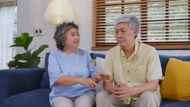 senior asian woman comforting the depression man while sitting on sofa at home living room, retirement people emotional - dementia stock videos & royalty-free footage