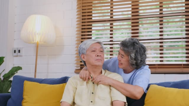 senior asian woman comforting the depression man while sitting on sofa at home living room, retirement people emotional - mental illness stock videos and b-roll footage