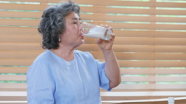 senior asian woman drinking milk in kitchen at home, retirement lifestyle, active senior healthy - soy milk almond milk stock videos & royalty-free footage