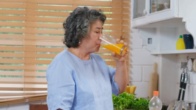 senior asian woman drinking orange juice in kitchen at home, retirement lifestyle, active senior healthy - juice drink stock videos & royalty-free footage