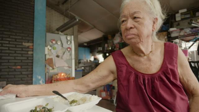 vidéos et rushes de haute femme asiatique manger un aliment à la maison. - dépression terrestre