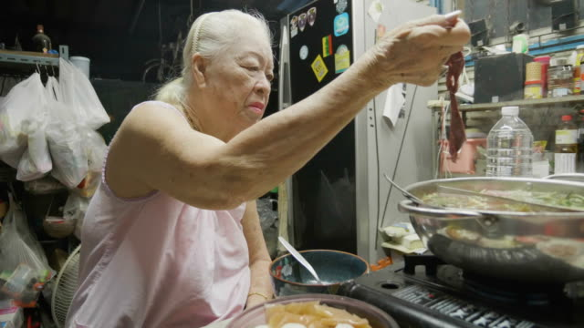 Senior Asian woman eating Suki or Shabu boiling in electric pot with turnips, pork chops, squid, corn, vermicelli and pork.Concept of: love, food, Asian food.