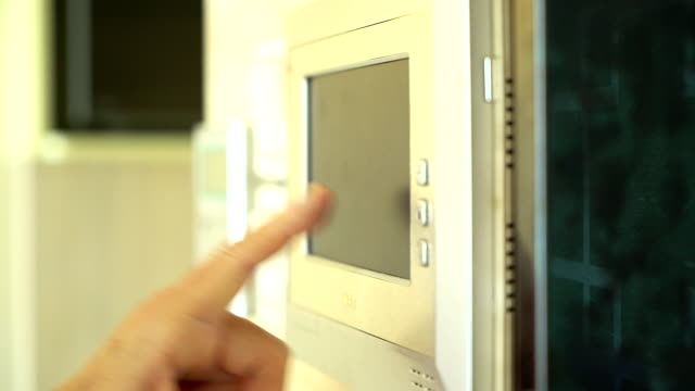 senior asian woman entering a code on the keypad of home security alarm. video intercom next to alarm keypad. - burglar stock videos & royalty-free footage