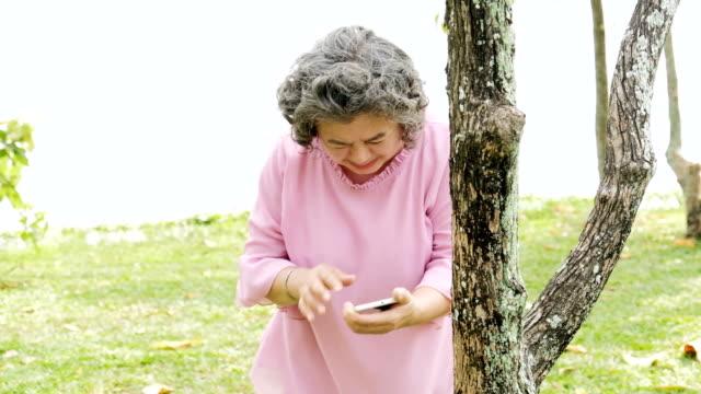 Senior Asiatin, Herzinfarkt, Schmerzen in der Brust und mit Smartphone für Hilfe.
