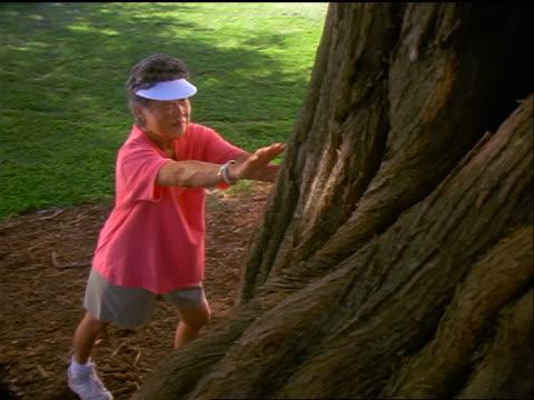 vídeos de stock, filmes e b-roll de senior asian woman leaning against tree + stretching / oahu, hawaii - só uma mulher madura