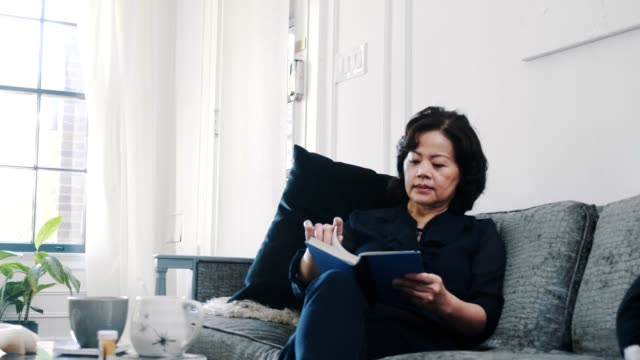 senior asian woman relaxes and reads a book in her home - prescription medicine home stock videos & royalty-free footage