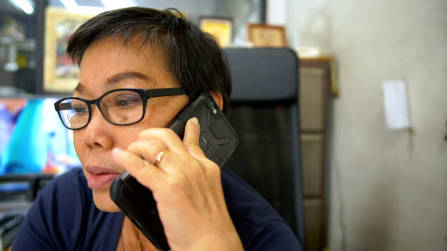 Senior Asian woman talking on smart-phone on office. connection concept connectivity.