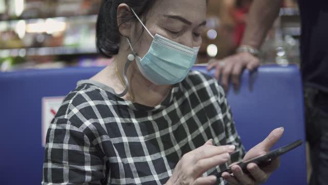 senior asiatische frau verwendet ein smartphone, um produkte online am flughafen zu sehen. - flugpassagier stock-videos und b-roll-filmmaterial