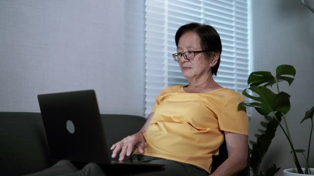 vidéos et rushes de femme asiatique senior utilisant l'ordinateur portable. - seniornaute