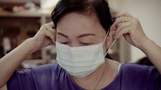 vídeos de stock e filmes b-roll de senior asian woman wearing protective mask in house. - ásia