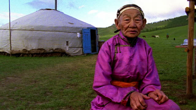 stockvideo's en b-roll-footage met ms portrait senior asian woman wearing traditional clothing sits outdoors with ger in background - mongolië